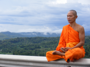 buddhist monk performing zen meditation on ledge overlooking mountains - Types of Meditation - PsychicStudent.com